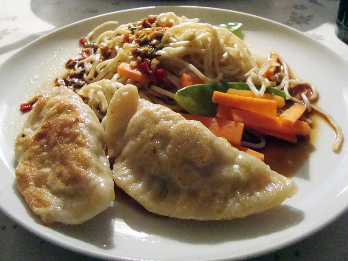 Kinesiske dumplings med dippingsauce, chow mein med grøntsager